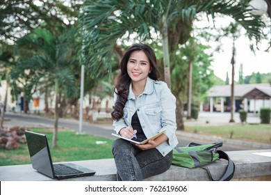 portrait of happy female college student using laptop at her campus park