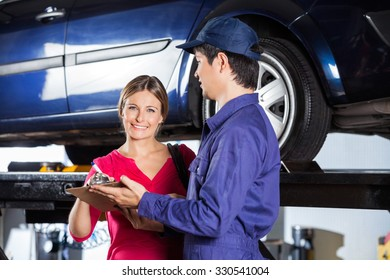 Portrait of happy female customer signing document while standing with technician in garage