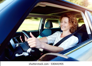 Portrait of happy female driver steering car with safety belt
