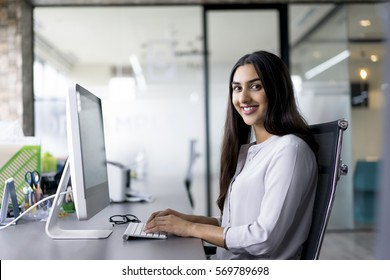 Portrait of happy female employee at computer