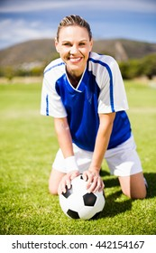 Portrait of happy female football player kneeling on field with ball