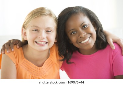 Portrait of happy female friends with arms around each other at home