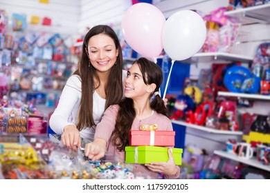 portrait of happy female and girl with gifts and balloons in the candy store