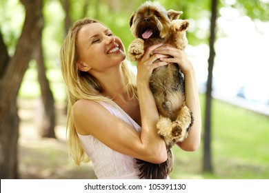 Portrait of happy female holding pet and looking at it in park