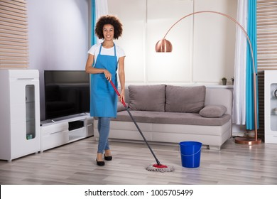 Portrait Of A Happy Female Housekeeper Cleaning Floor With Mop