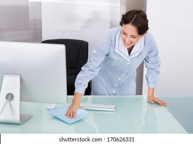 Portrait Of Happy Female Janitor Cleaning Desk At Office