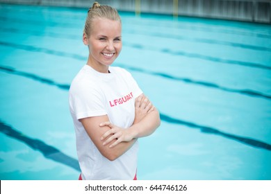 Portrait of happy female lifeguard standing at poolside