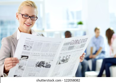 Portrait of happy female reading newspaper in working environment
