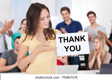 Portrait Of A Happy Female Student Holding Board With Thank You Text