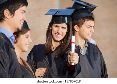 Portrait of happy female student showing diploma while standing with friends at college
