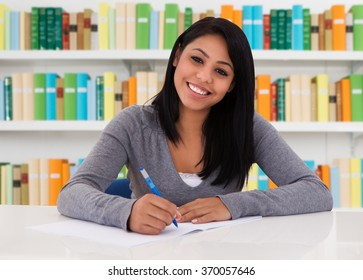 Portrait of happy female student sitting at desk in library