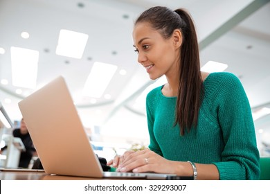 Portrait of a happy female student using laptop computer in university