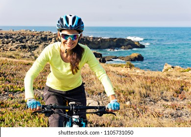 Portrait of a happy female  tourist cyclist riding mountain bike on a ocean rocky coast, looking at the camera and smiling. Europe. Portugal.