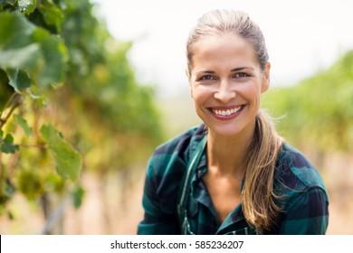 Portrait of happy female vintner in the vineyard
