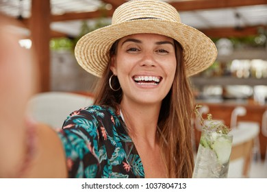 Portrait of happy females with broad smile, dressed in fashionable blouse and straw hat, makes selfie and shares photos in social networks with friends, stands against bar interior. Lifestyle concept