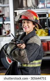 Portrait of happy firewoman holding walkie talkie while standing against firetruck at station