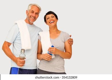 Portrait of a happy fit couple against grey vignette