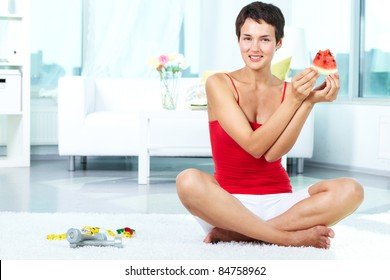 Portrait of happy fit female holding piece of watermelon