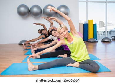 Portrait of happy fit woman with friends exercising on mats in fitness club