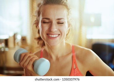 Portrait of happy fit woman in sport clothes in the modern living room lifting dumbbell.