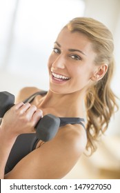 Portrait of happy fit young woman lifting weights at gym