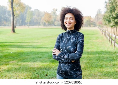 Portrait of happy Fitness African woman relaxing after exercise on green fields in the morning. Copy space for your motivation text.