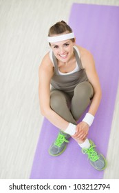 Portrait of happy fitness woman sitting on fitness mat