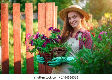 Portrait of happy florist gardener with flower pot of petunia outdoors. Gardening and floriculture. Growing flower in home garden