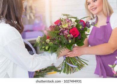 Portrait of a happy florist offering and sale flowers at the counter in the florist shop