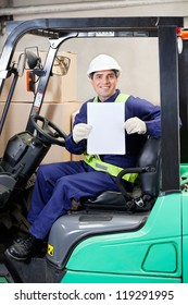 Portrait of happy forklift driver displaying blank placard