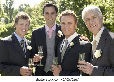 Portrait of happy four men holding champagne flutes at wedding day