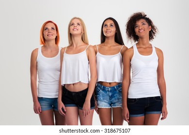 Portrait of a happy four women looking up isolated on a white background