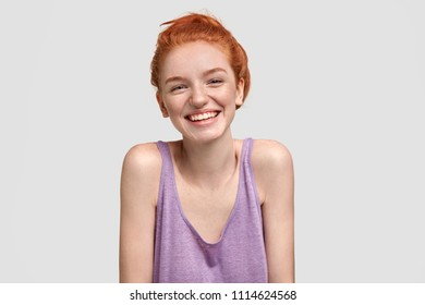 Portrait of happy freckled female with ginger hair, has broad smile, glad to meet with someone, dressed in oversized purple t shirt, isolated over white background. Red haired teenager indoor