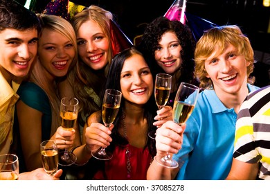 Portrait of happy friends with champagne at birthday party