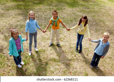 Portrait of happy friends standing on the ground in park and looking at camera