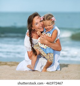 portrait of Happy fun Mother and small daughter on beach, laughing, outdoor, Spain