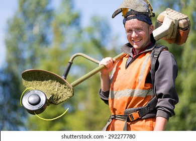 Portrait happy gardener or road landscaper man worker with gas grass trimmer equipment