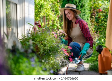 Portrait of happy gardening woman in gloves, hat and apron plants flowers on the flower bed in home garden. Gardening and floriculture. Flower care