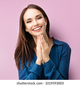 Portrait of happy gesturing smiling young woman in casual smart blue clothing, over pink background
