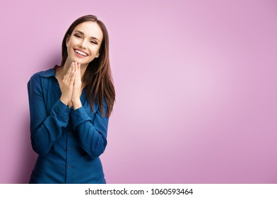 Portrait of happy gesturing smiling young woman in casual smart blue clothing, pressing palms together, over purple background, with copyspace for slogan, advertising or text message