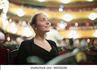 Portrait of happy girl in auditorium of opera teatre
