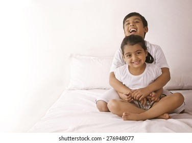 Portrait of happy girl being embraced by brother in bed
