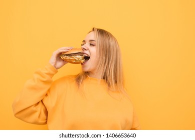 Portrait of a happy girl bites a delicious large burger with her eyes closed on a yellow background, wearing orange clothing. The hungry girl eats calories, isolated on a yellow background.
