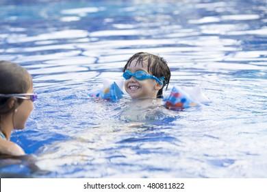 Portrait of Happy Girl and Boy Enjoying in Swimming Pool