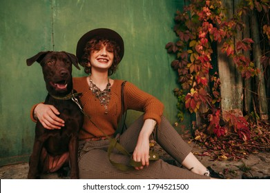 Portrait of happy girl in fashionable clothes hugging on background of green wall with ivy, wearing vintage clothes sitting on street near country house. Village girl with dog resting on the street.