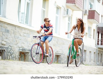 Portrait of happy girl and guy cycling at leisure