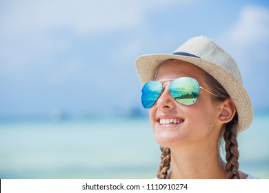 Portrait of happy girl in hat and sunglasses on beach. Summer vacation concept