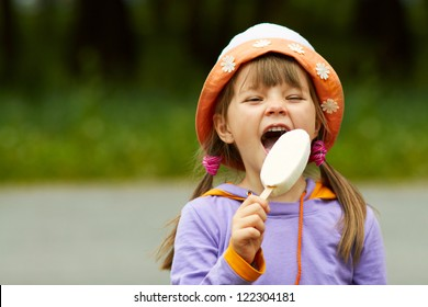 portrait of happy girl in a hat who eats ice cream