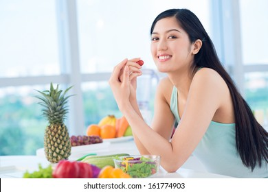Portrait of a happy girl having a healthy snack of fresh fruit and vegetables