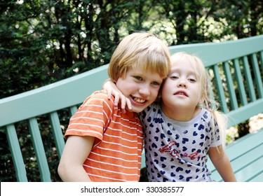 Portrait of happy girl with her autistic brother outdoors